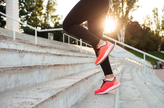 Cropped photo of strong young sports woman running on steps outdoors.